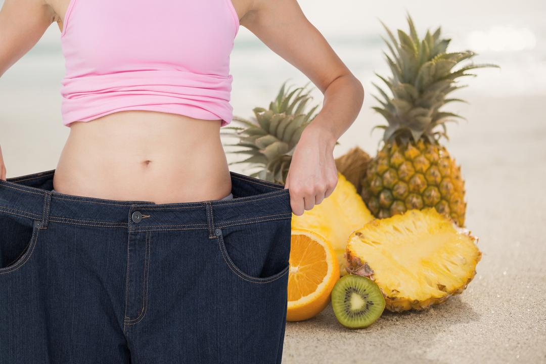 Digital composite of Midsection of woman in loose jeans by pineapples representing weight loss