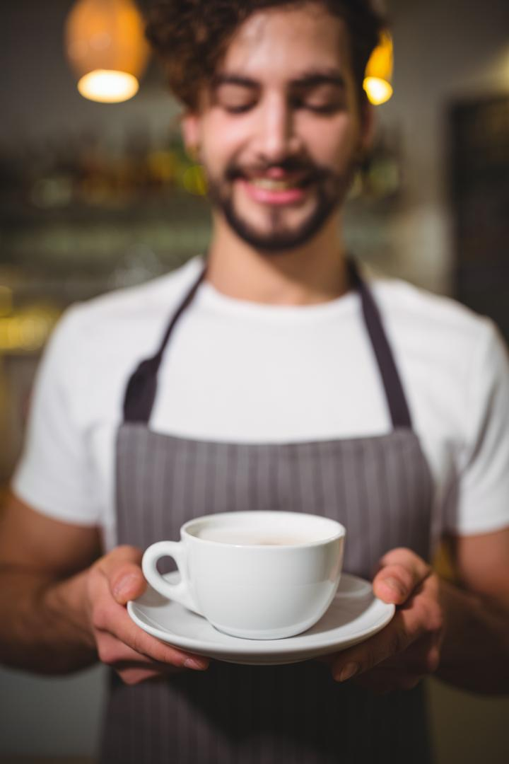 Smiling waiter holding cup of coffee in café