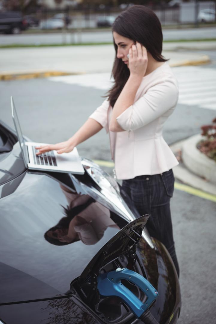 Beautiful woman talking on mobile phone while charging electric car on street