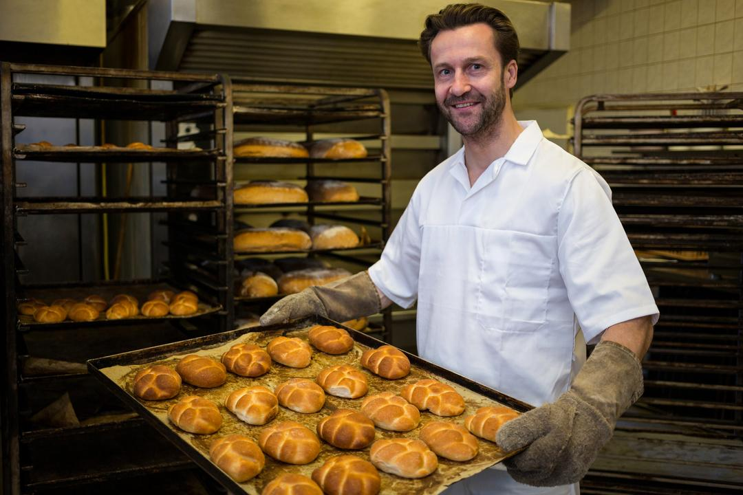 Portrait of smiling baker carrying a tray of baked buns