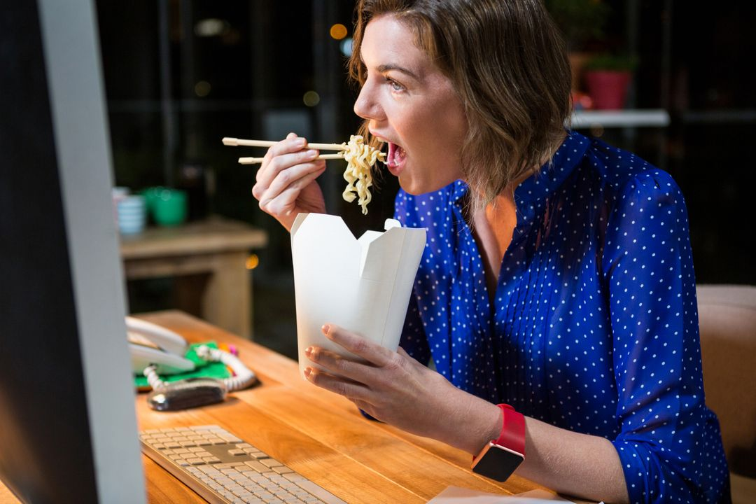 Businesswoman eating noodles at her desk in the office Free Stock Images from PikWizard