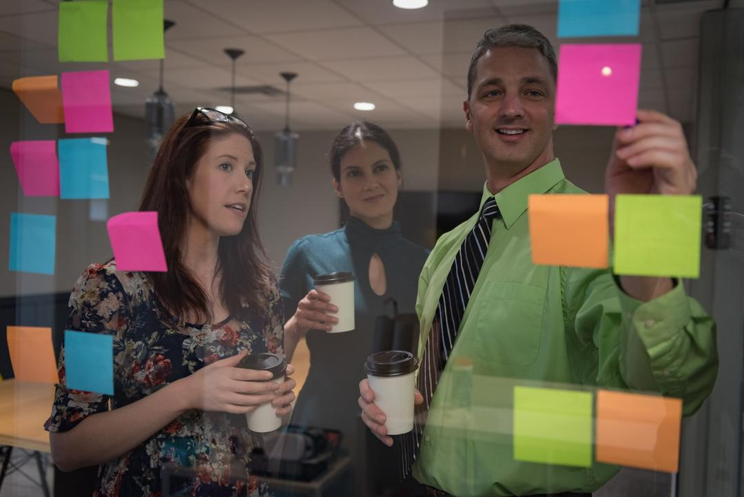 Business colleagues discussing over sticky notes seen through glass in office