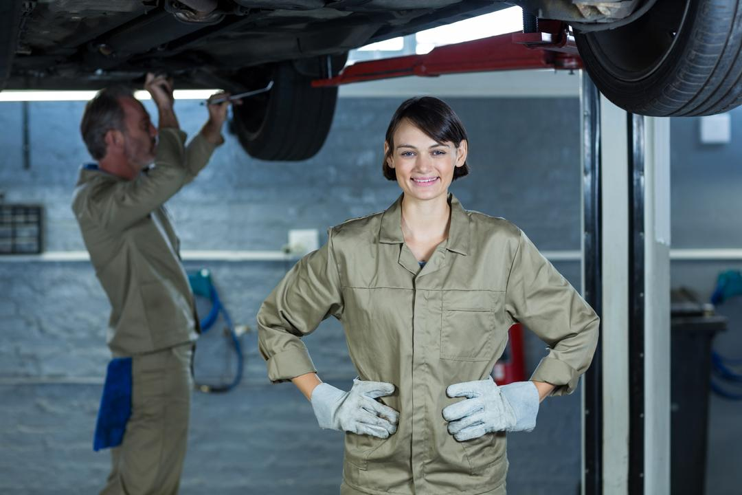 Portrait of smiling female mechanic standing with hands on hip at repair shop