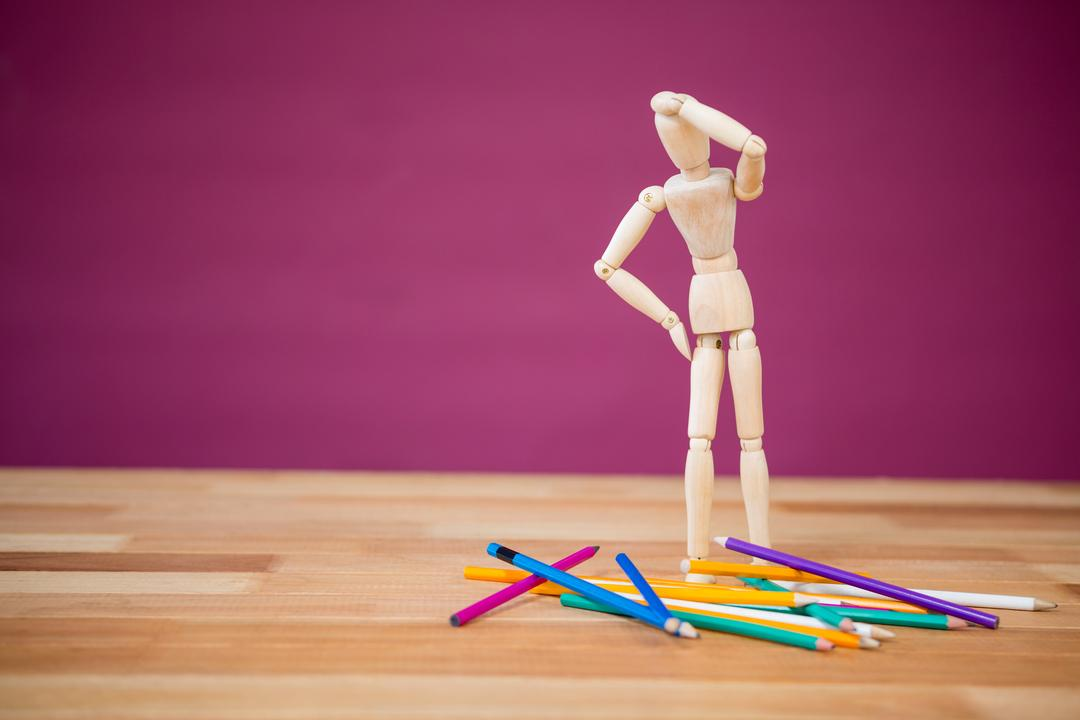 Conceptual image of figurine looking at pencil