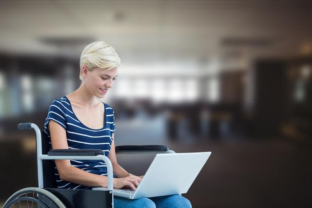 Businesswoman using laptop in wheelchair over blurred background