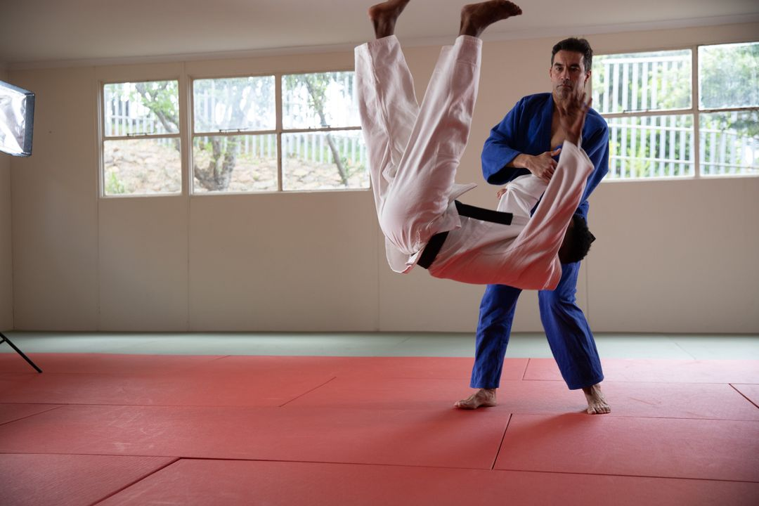 Caucasian and African American male judokas wearing blue and white judogi, practicing judo on a mat during a training in a bright studio. Free Stock Images from PikWizard