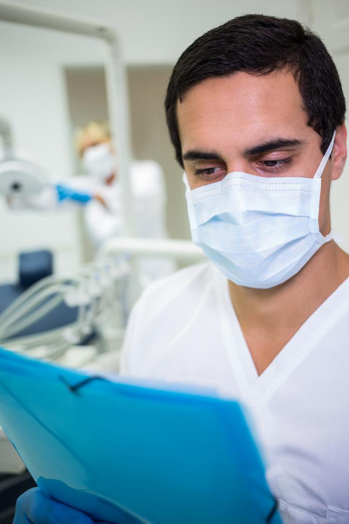 Dentist in surgical mask looking at a medical file in dental clinic
