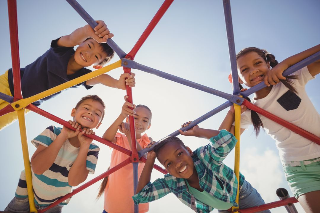 Portrait of happy schoolkids looking through dome climber at school playground Free Stock Images from PikWizard