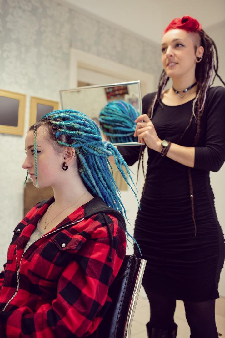 Beautician styling clients hair in dreadlocks shop Free Stock Images from PikWizard