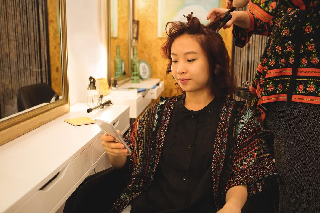 Woman using mobile phone while getting her hair straightened at hair saloon Free Stock Images from PikWizard