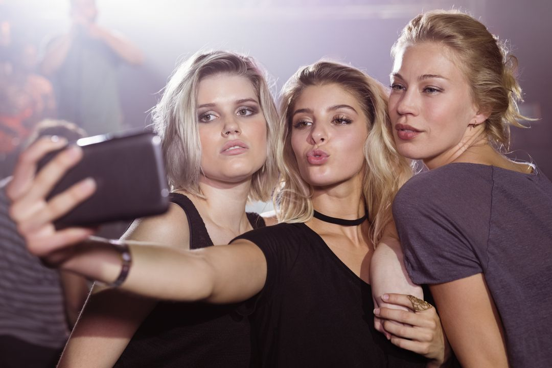 Young female friends taking selfie through mobile phone at nightclub Free Stock Images from PikWizard