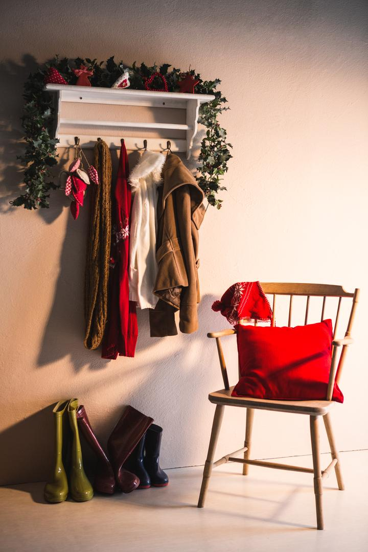 Winter clothes hanging on hook hanger and wooden chair