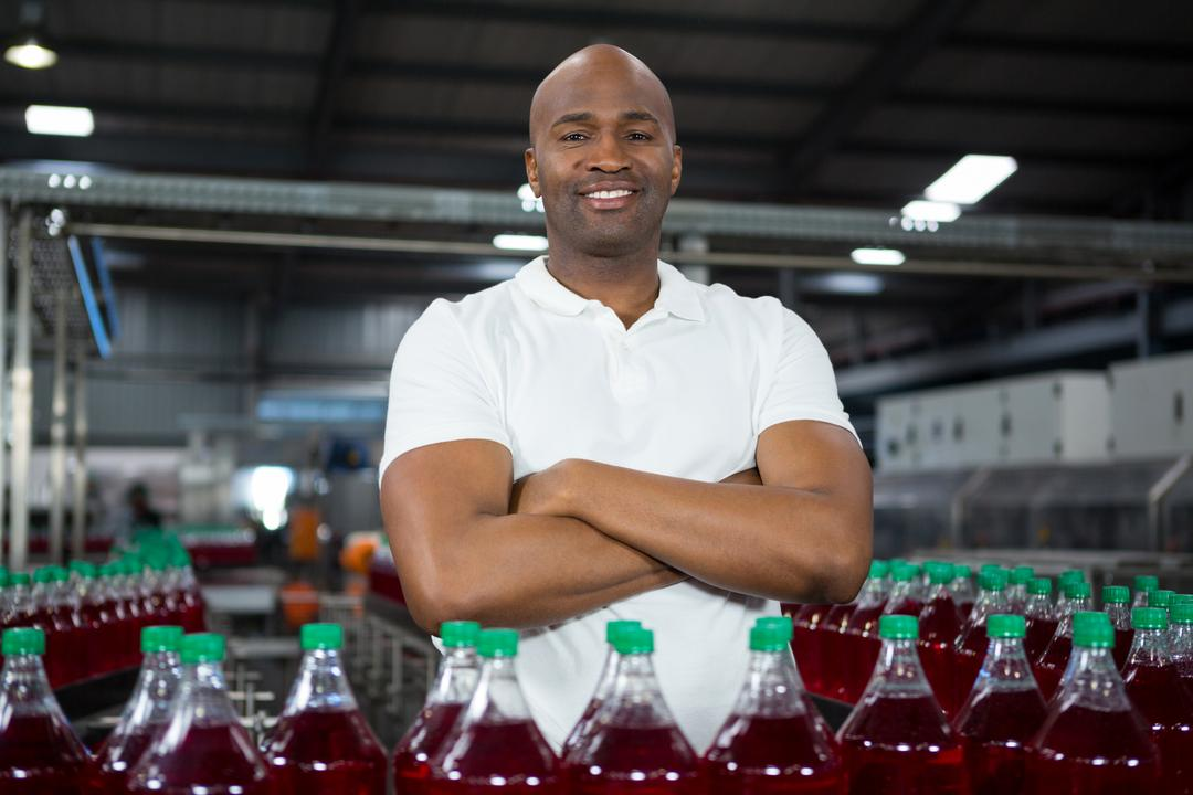 Portrait of confident male worker operating machine in cold drink factory