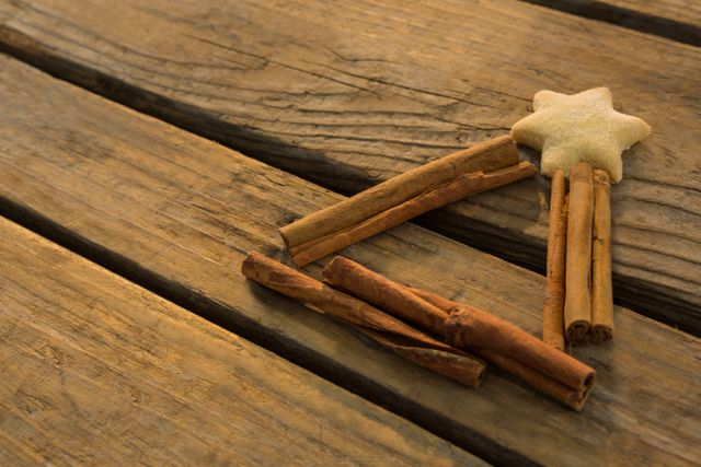 High agnle view of star shape cookie with cinnamon sticks on wooden table