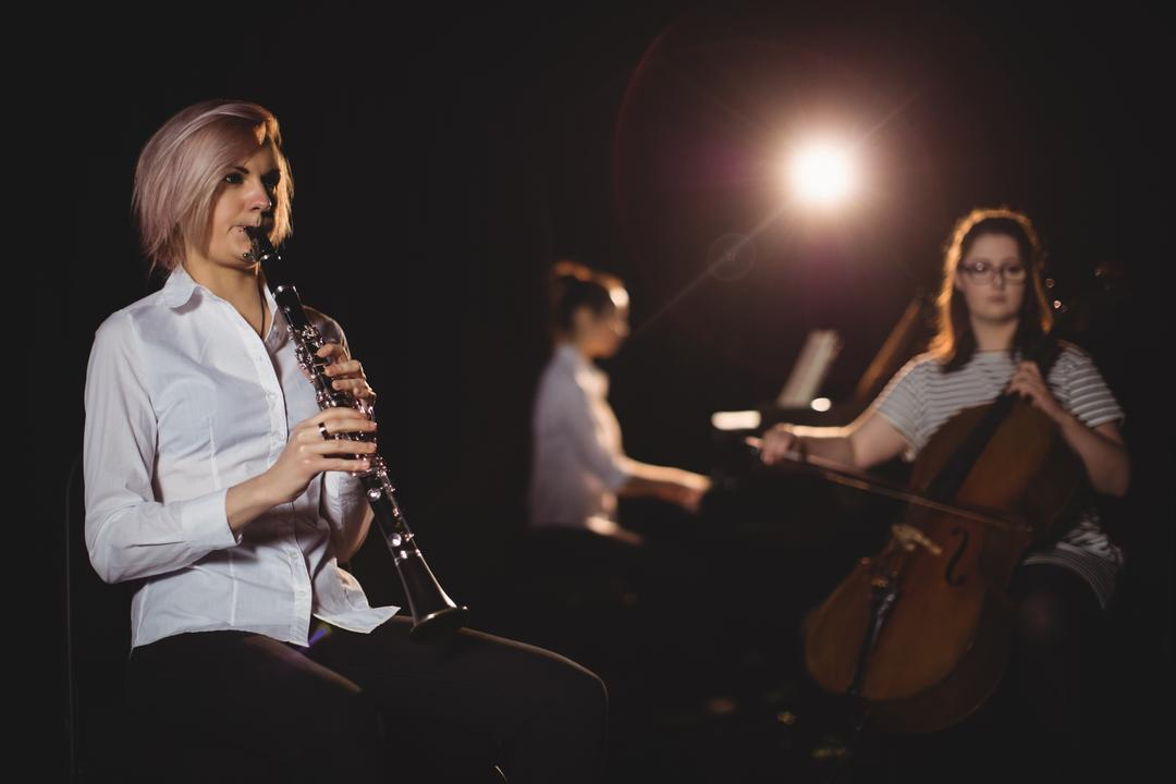 Three female students playing double bass, clarinet and piano in a studio