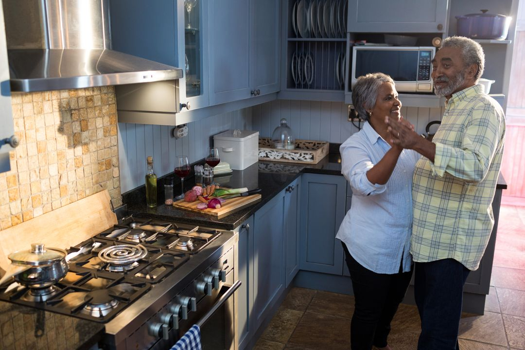 Smiling senior couple dancing in kitchen at home Free Stock Images from PikWizard