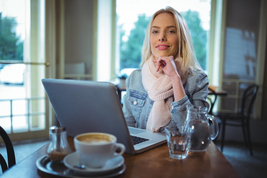 Portrait of smiling woman using laptop while having coffee in café Free Stock Images from PikWizard