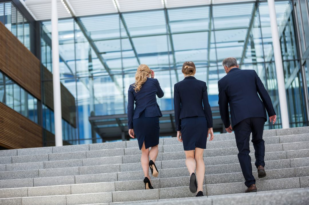 Businesspeople climbing up the steps in office premises