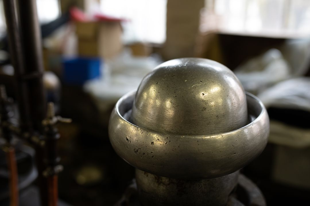 Close up view of a shiny metal object for creating hat shapes in the workshop at a hat factory.
