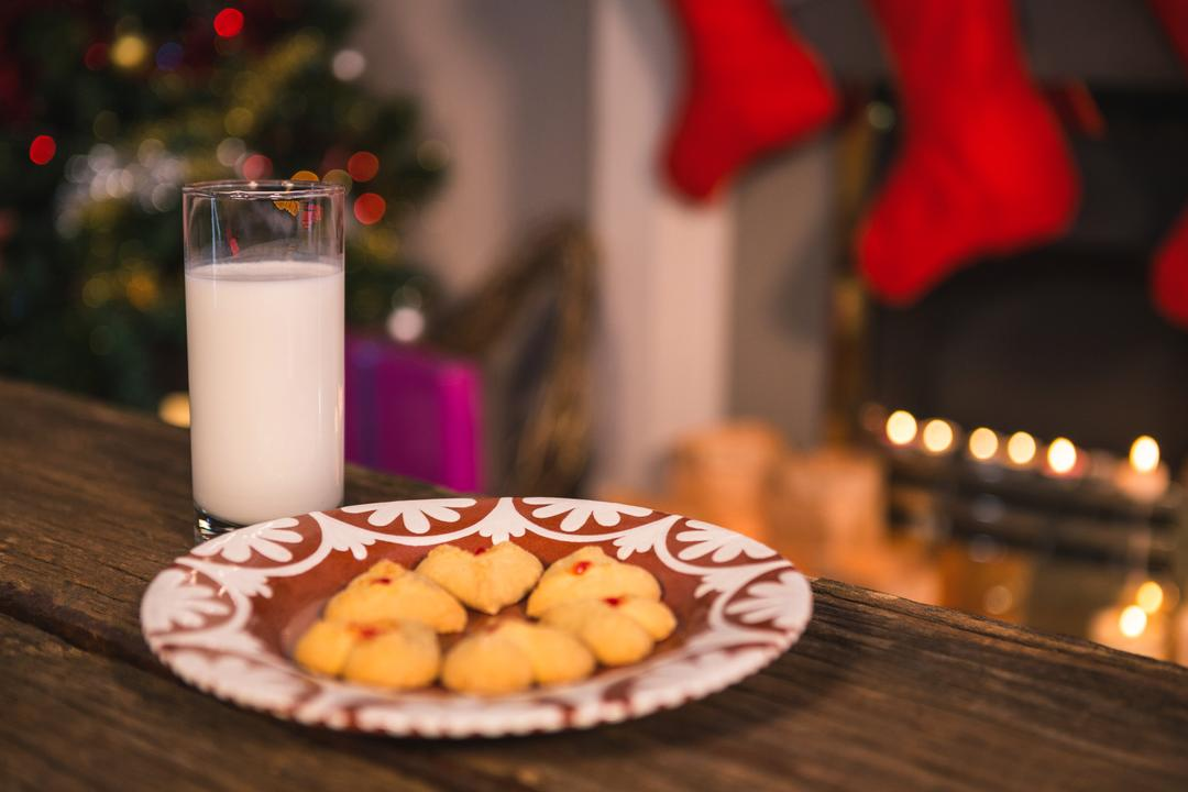 Christmas cookies on plate with a glass of milk on wooden table during christmas time