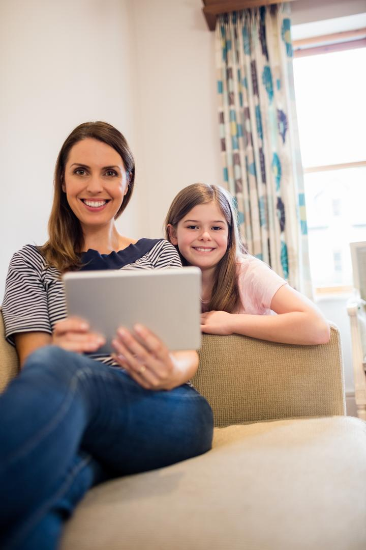 Mother and daughter sitting on sofa using digital tablet in living room at home