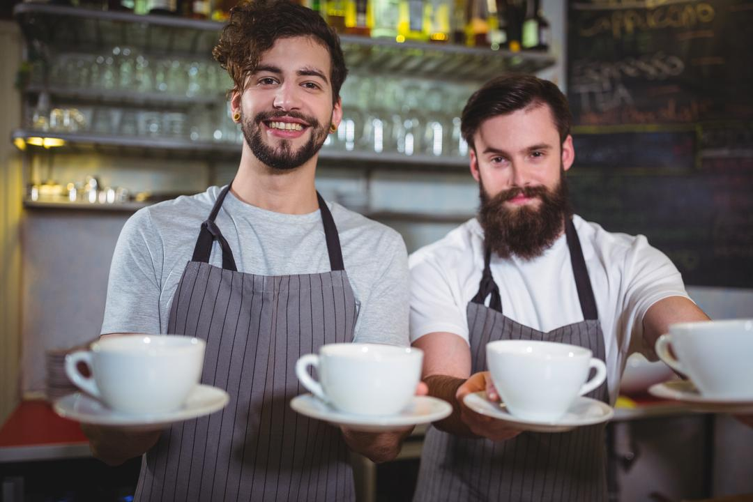 Portrait of smiling waiters serving a cup of coffee at counter in café