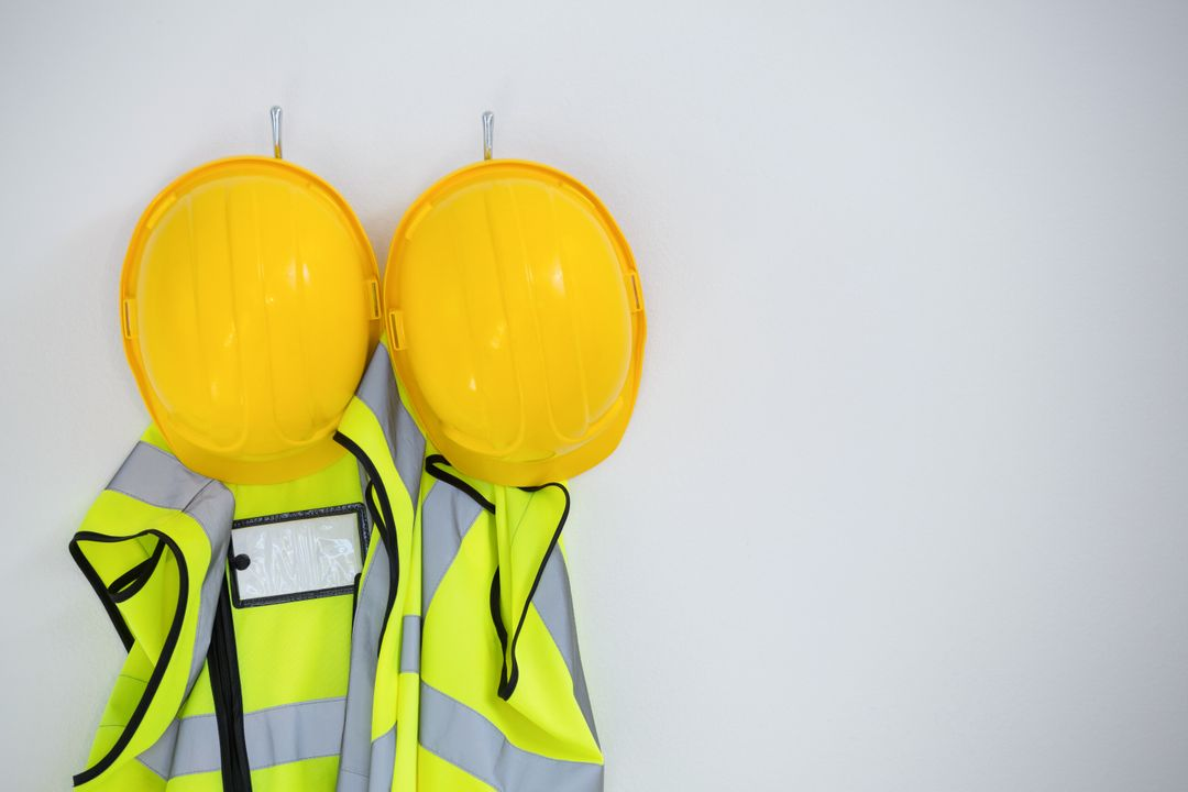 Close-up of protective workwear hanging on hook against white background Free Stock Images from PikWizard