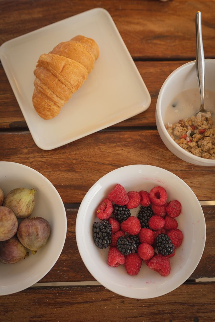 High angle close up of healthy breakfast with berries, figs, cereal in bowls and croissant on plate. Source of vitamin C during coronavirus Covid 19 pandemic. Free Stock Images from PikWizard