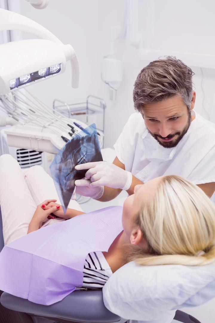 Dentist showing x-ray to the patient in clinic Free Stock Images from PikWizard