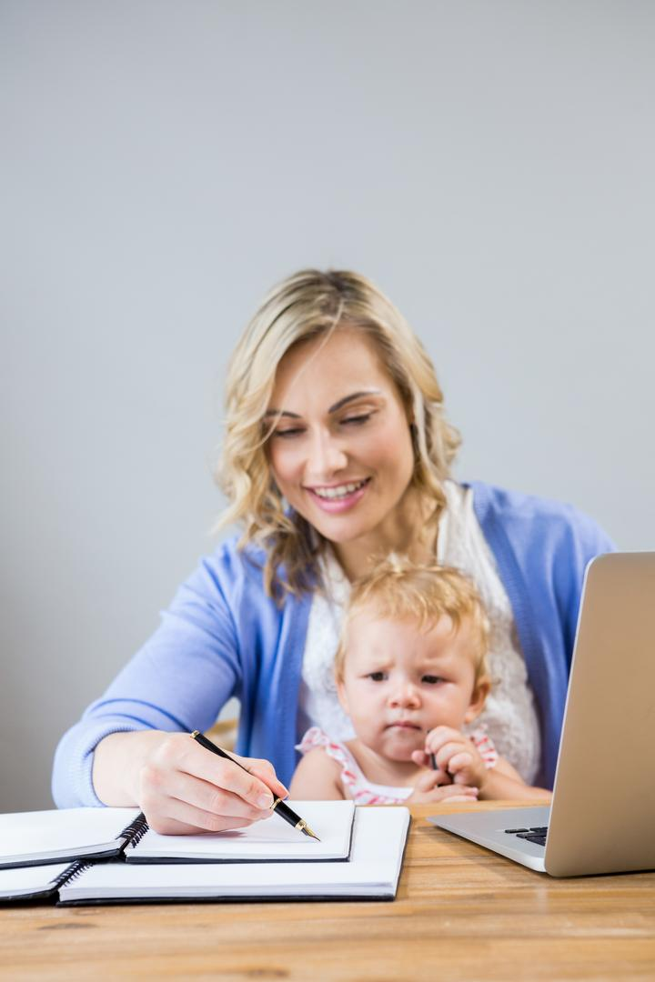 Mother holding baby girl while writing notes in personal organizer at home Free Stock Images from PikWizard