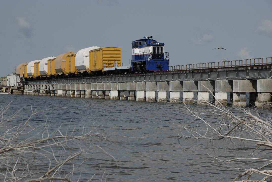 CAPE CANAVERAL, Fla. – The NASA Railroad hauls cars carrying the Ares I-X motor segments and nozzle exit cone over a river bridge to NASA's Kennedy Space Center in Florida.  The four reusable motor segments and the nozzle exit cone, manufactured by the Ares I first-stage prime contractor Alliant Techsystems Inc., or ATK, departed Utah March 12 on the seven-day, cross-country trip to Florida.  The segments will be delivered to Kennedy's  Rotation, Processing and Surge Facility for final processing and integration. The booster used for the Ares I-X launch is being modified by adding new forward structures and a fifth segment simulator. The motor is the final hardware needed for the rocket's upcoming test flight this summer. The stacking operations are scheduled to begin in the Vehicle Assembly Building in April.   Photo credit: NASA/Kim Shiflett