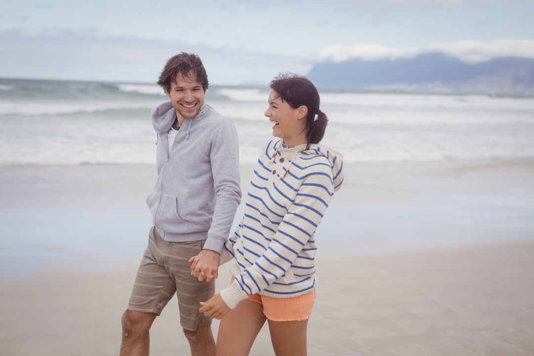Happy young couple holding hands while walking at beach Free Stock Images from PikWizard
