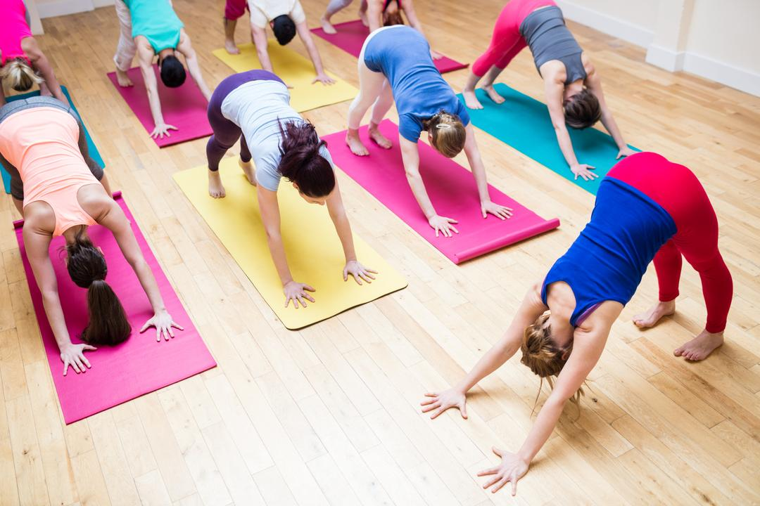 Trainer assisting group of people with downward dog pose yoga exercise in the fitness studio