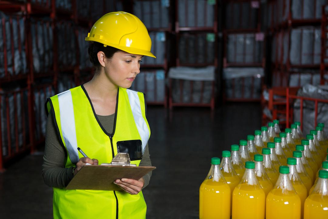 Young female worker examining juice bottles in factory