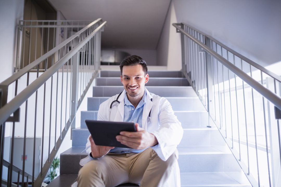 Portrait of smiling doctor sitting on staircase using digital tablet in hospital Free Stock Images from PikWizard