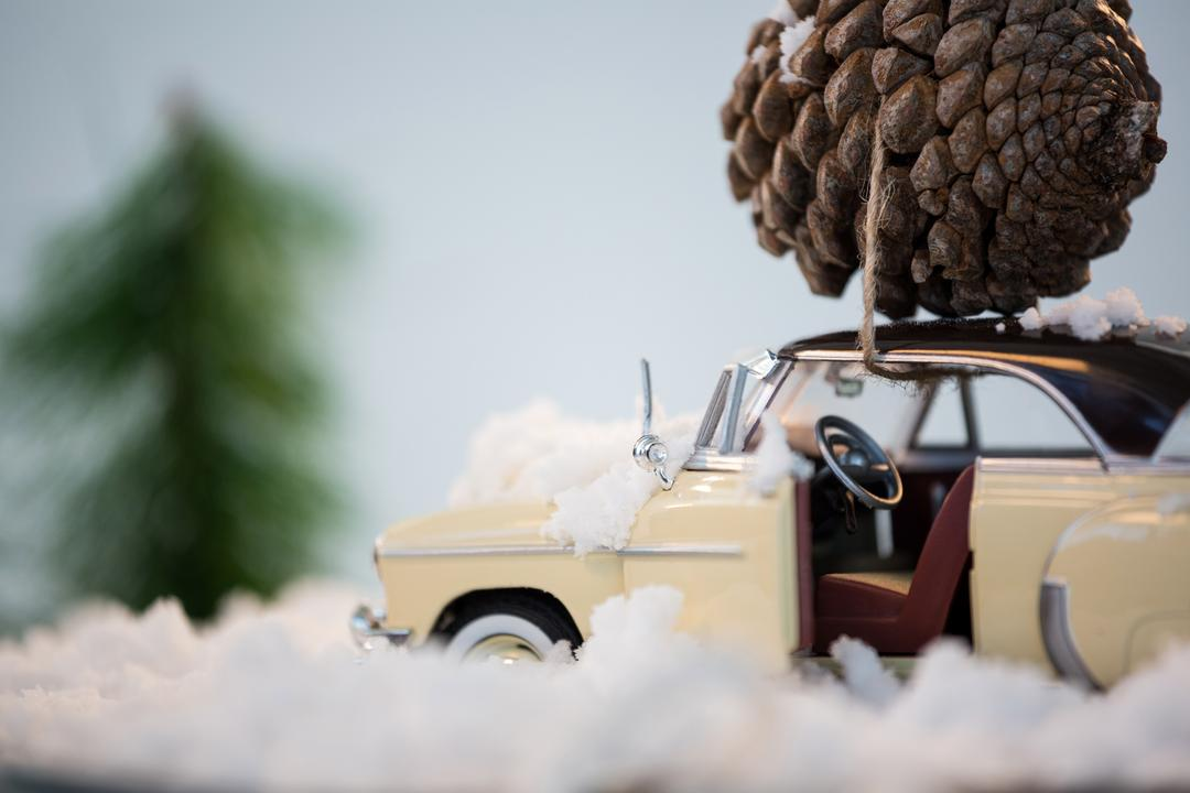 Toy car carrying pine cone on fake snow during christmas time Free Stock Images from PikWizard