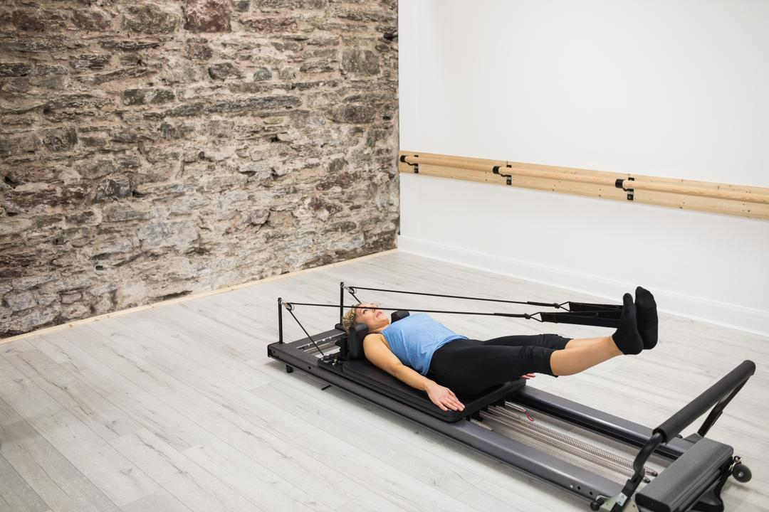Woman exercising on reformer in gym Free Stock Images from PikWizard