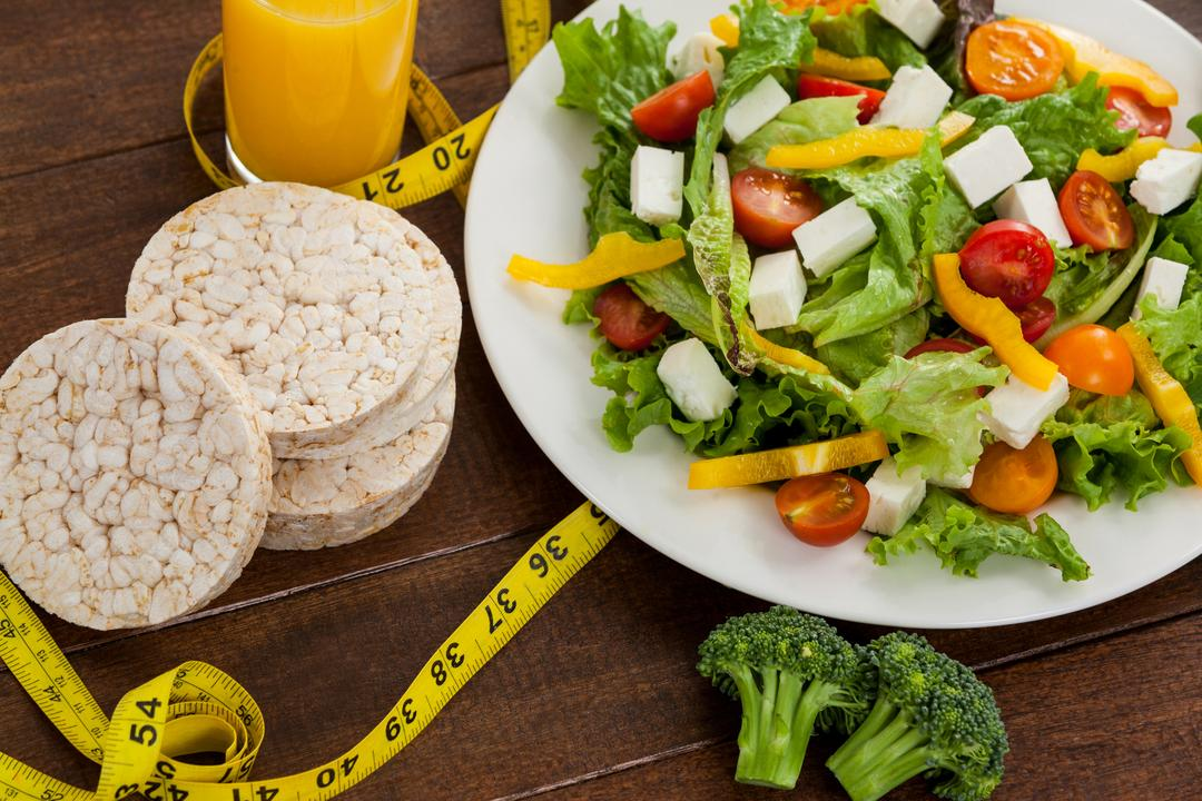 Salad, juice, edible bars and measuring tape on table - diet concept