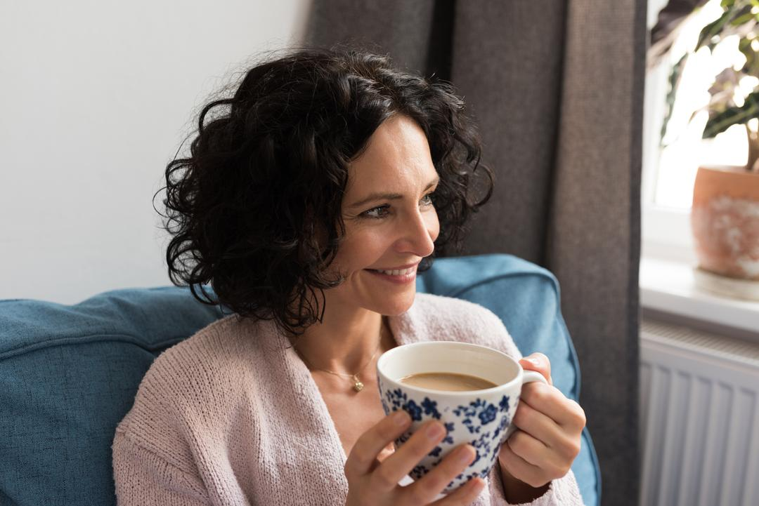 Beautiful woman holding a coffee cup at home