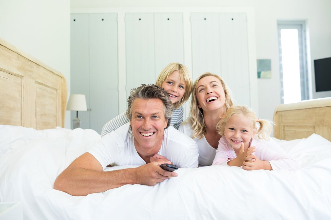 Happy family watching television in the bed room at home Free Stock Images from PikWizard