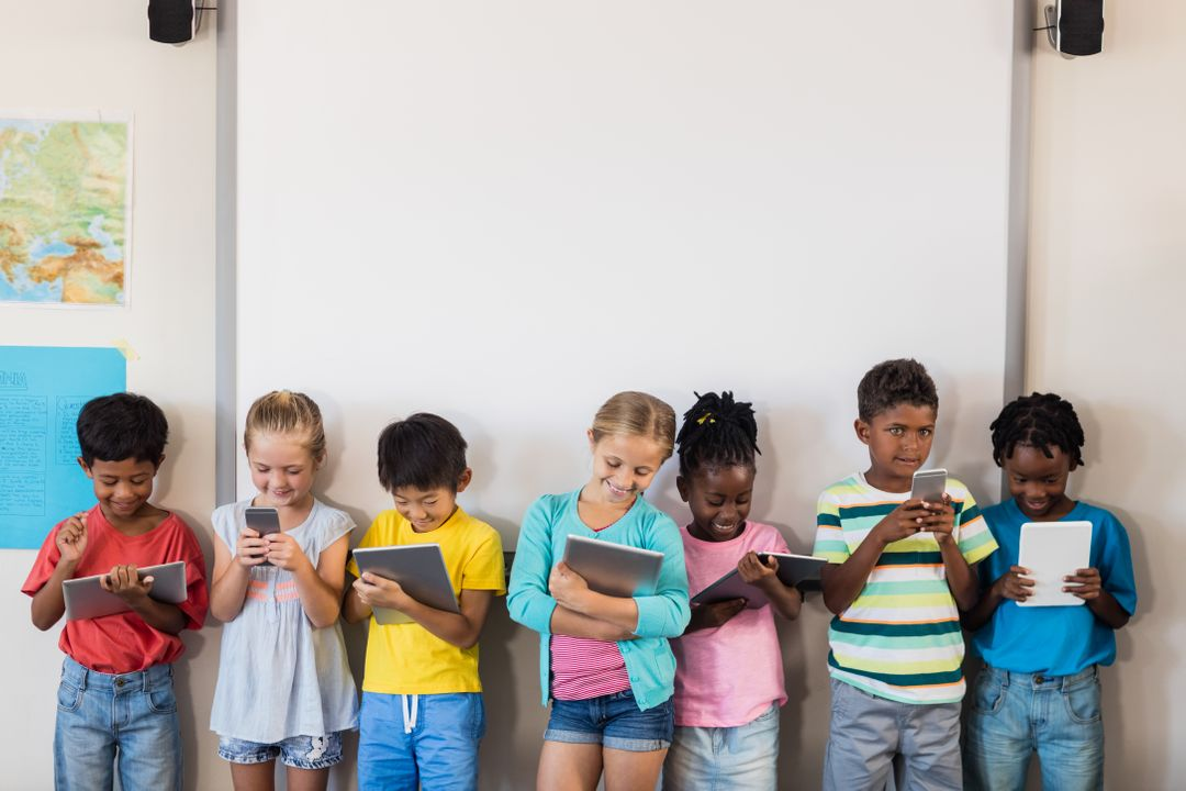 Children standing watching videos on their tablets