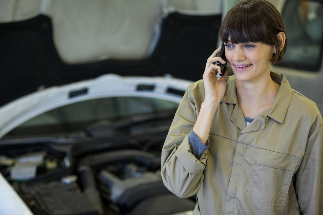 Female mechanic talking on a mobile phone at the repair garage Free Stock Images from PikWizard