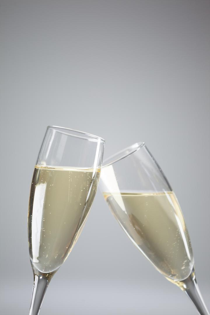 Close-up of two champagne flutes on white background
