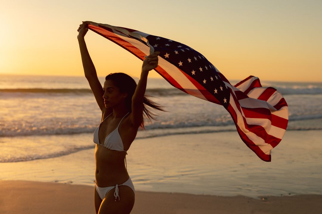 Young woman standing with waving American flag on the beach