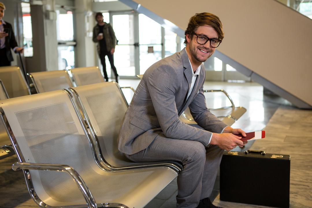 Businessman with passport, boarding pass and briefcase sitting in waiting area at airport terminal