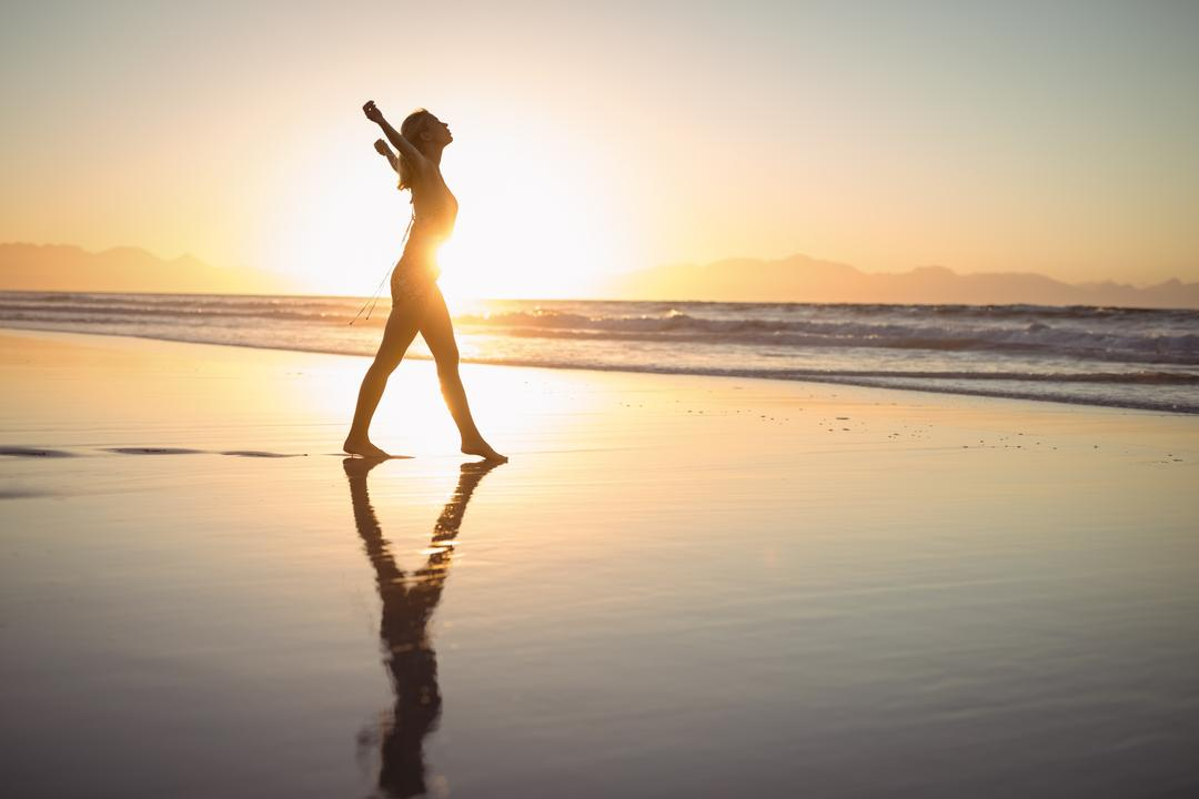 Side view of silhouette woman with arms outstretched walking on shore at dusk