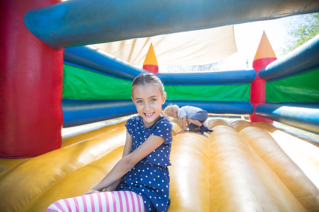 Portrait of happy girl sitting on bouncy castle while brother playing in background Free Stock Images from PikWizard