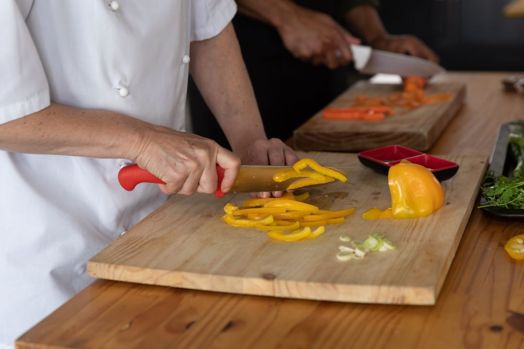 Image of a Cook Cutting Peppers on a Chopping Board