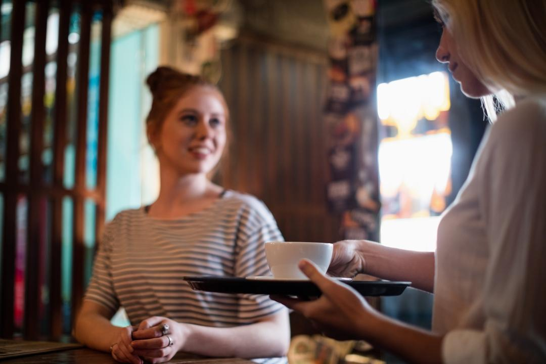 Waitress serving coffee to the woman in the bar