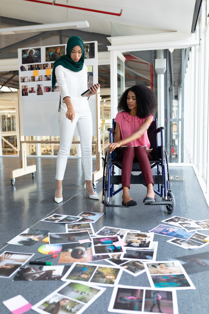 Front view of diverse female graphic designers discussing on photographs in office. This is a casual creative start-up business office for a diverse team